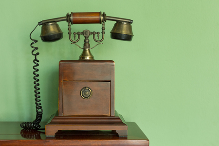 telefono antico: Wooden and brass antique telephone in classic style on top of a wooden table with green background.