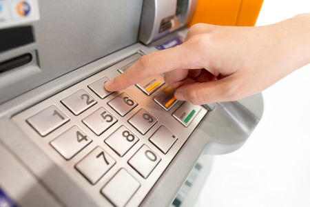 machine: Lady using ATM machine to withdraw her money.