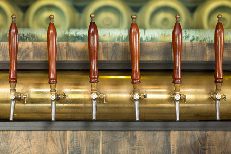 pump: Beer taps inside a pub with beer buckets in the background. Stock Photo
