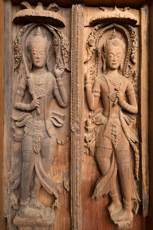 guardians: Ancient wooden crafted door panel with guardians sculpture decorated. Stock Photo