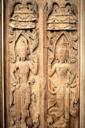 wood carving door: Ancient wooden crafted door panel with guardians sculpture decorated in vintage and grunge tone.