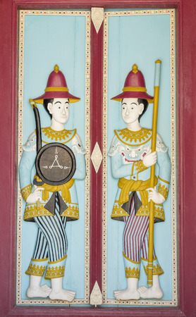 ancient soldiers: Wooden doors panel at thai temple with crafted ancient soldiers on each side. Stock Photo