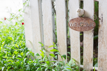 sign post: Rustic welcome sign on white wooden fence with selective focus.