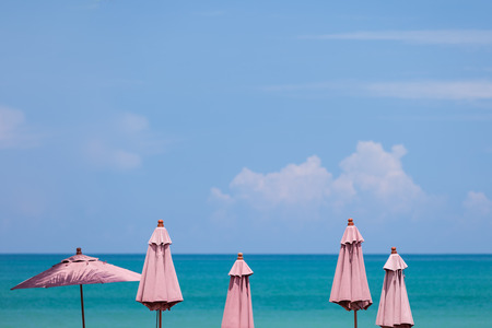 turquise: Red umbrellas by the turquise sea and blue sky with soft focus.