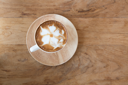 calor: Cup of cappuccino with latte art on a wooden plate and wooded table