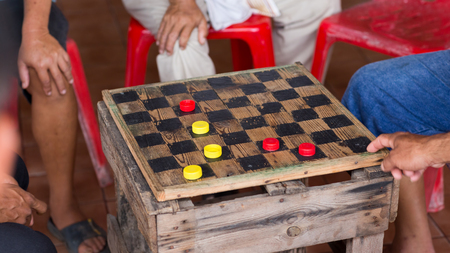 checker: group of men are having fun  playing checker ,draught, game.
