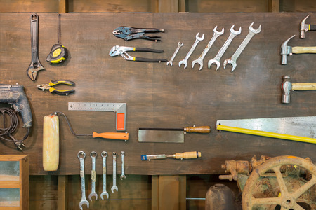 Equipment and hand tools hanged on a wooden board.