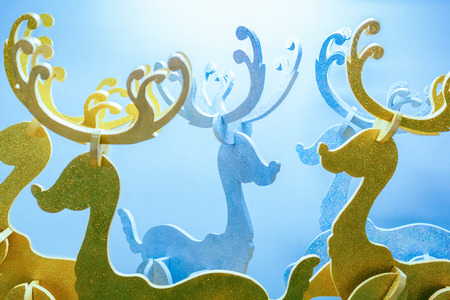 tint: Group of decorated foam reindeer for Christmas holiday with shiny golden and silver color against white backdrop with blue tint.