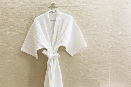 house robe: White shower gown  hanged in the bathroom with stone tiles wall background.