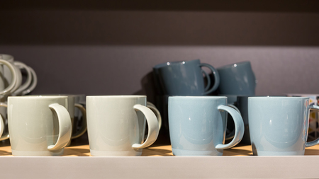earth tone: Earth tone color ceramic coffee cups in a sideboard.