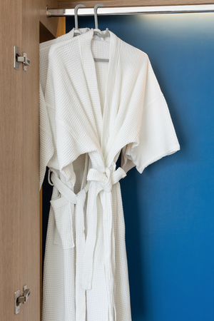 bath gown: Two white shower gown hanged in the closet with blue background. Stock Photo