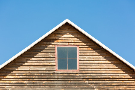 house gable: Gable of a wooden house with a window in the middle against blue sky.