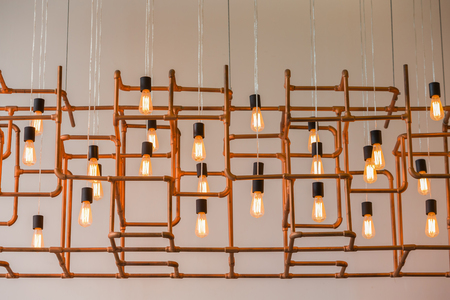 living style: Vintage style light bulbs hang and decorated with alloy pipes in a living room