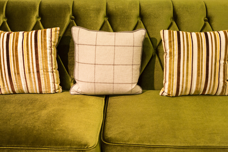 Close up of green velvet sofa and cushions with vintage style.