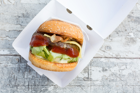 tomate: Beef burger with cheese and bacon in white paper box on white wooden table. Banque d'images
