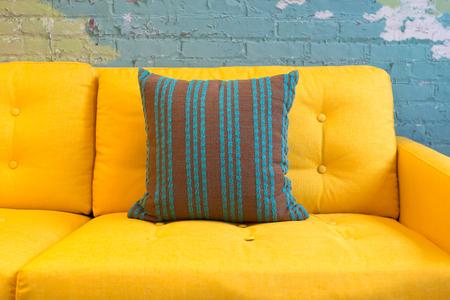 Close-up van gele stof bank en kussens met vintage stijl tegen blauwe bakstenen muur.
