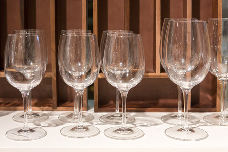 banquet table: Empty wine glasses in a banquet on white table and wooden wall. Stock Photo