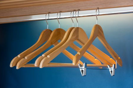 closet rod: Close up of wooden hangers inside a blue closet with selective focus on the stainless pin.