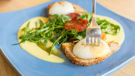 poke: Egg benedict on a blue plate with a fork poke on the yolk. Stock Photo