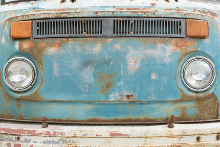 Front panel of old and rusty car,  focus on paint and rusty and front head lights in retro tone.