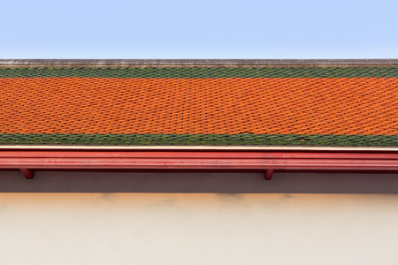 wallpaper pattern: old style orange and green clay tiles roof top against nice blue sky.