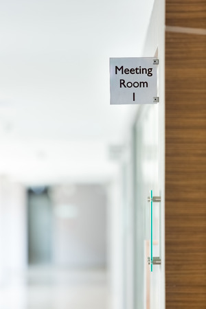 Meeting room sign on the glass door inside an office building.