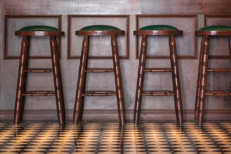 Fila de taburetes de madera en frente del mostrador de madera en el interior de un bar de estilo vintage. Foto de archivo