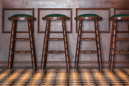 Row of wooden stools in front of wooden counter inside a vintage style bar.