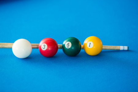 pool stick: Colorful pool balls and pool stick on a blue table.