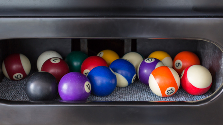 pool balls: Pool balls in a inside table pocket .