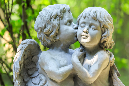 Little couple angel sculpture in green garden