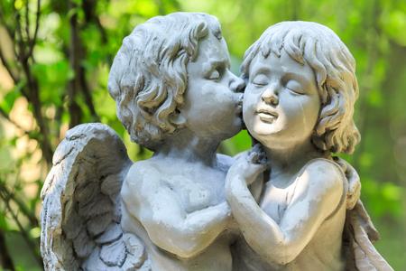 angel cemetery: Little couple angel sculpture in green garden