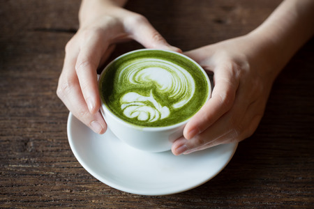 Lady hand holding a white cup of matcha Latte , Green Tea, on Wooden Background table. Stock Photo