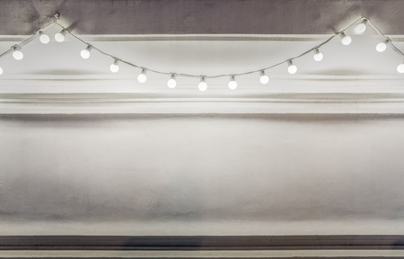 Background of light bulbs string decorated on a white wall at night.