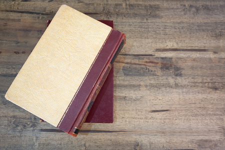 hard cover: Old book with hard cover on a wooden desk.