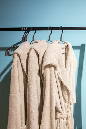 house robes: Three off white bath gown hanged on the rack with blue background. Stock Photo