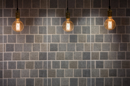 down lights: Industrial and Vintage style lighting bulbs with stone tiles background.