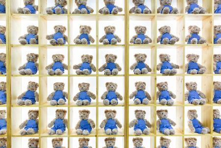 smock: Backdrop of Bear dolls wear jean smock on wooden shelves. Stock Photo