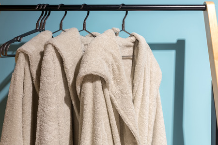 housecoat: Three off white bath gown hanged on the rack with blue background. Stock Photo