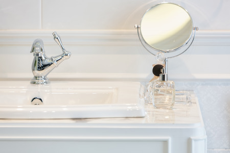 Perfume bottles on  white washbasin counter top inside a classic style bathroom.