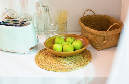 Toaster, wooden plate full of green apples and wicker basket on a white counter in a clean kitchen. Stock Photo