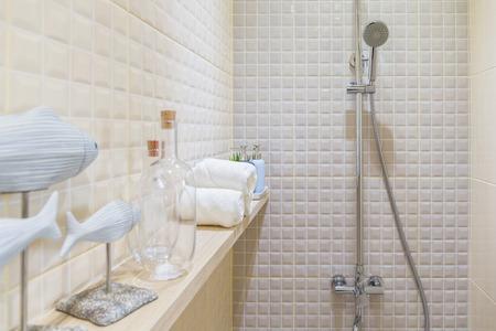 shelf: Shower room with decoration items on a wall shelf.