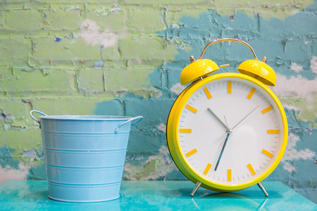Big yellow retro style alarm clock and blue metal bucket decorated  in a living room with colorful brick wall