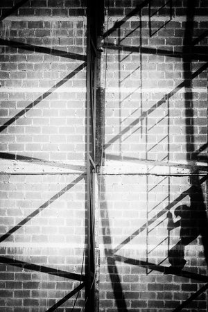b w: abstract of worker and shadow climbing ladders in construction site in black and white. Stock Photo