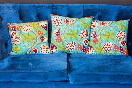 blue velvet: Green indian style cushions on a blue velvet sofa.
