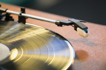 Old style gramophone and black vinyl disk. Stock Photo