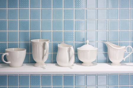 Weiße keramische Flasche und Cup auf weißem Regal mit blauer Fliesenwand. Standard-Bild - 70200792