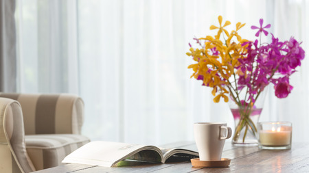 Cup of coffee on a wooden tea table with an opened book and orchid flower with Cozy armchair in a bright room with white curtain background.