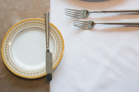 Luxury porcelain ware and silverware on white dining table. Stock Photo