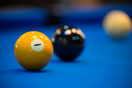 Colorful pool balls on a blue table.